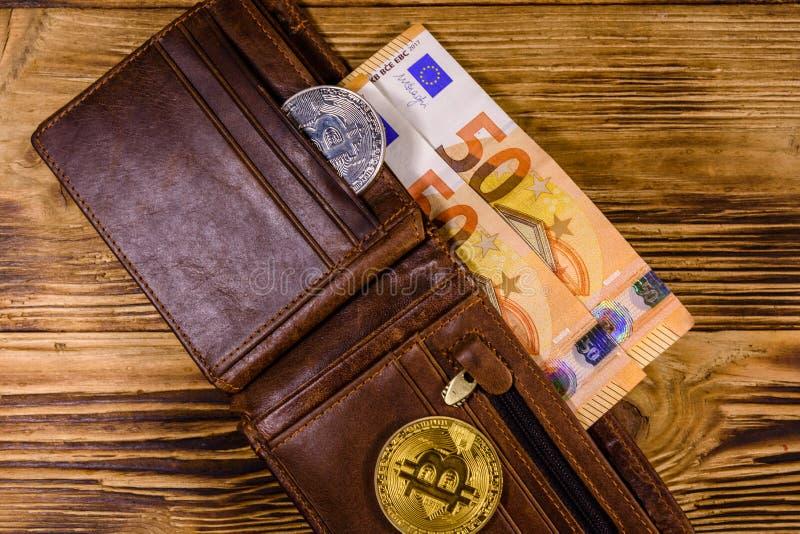 Brown rzemienny portfel z pi??dziesi?t euro bitcoins na drewnianym tle i banknotami Odg?rny widok fotografia stock
