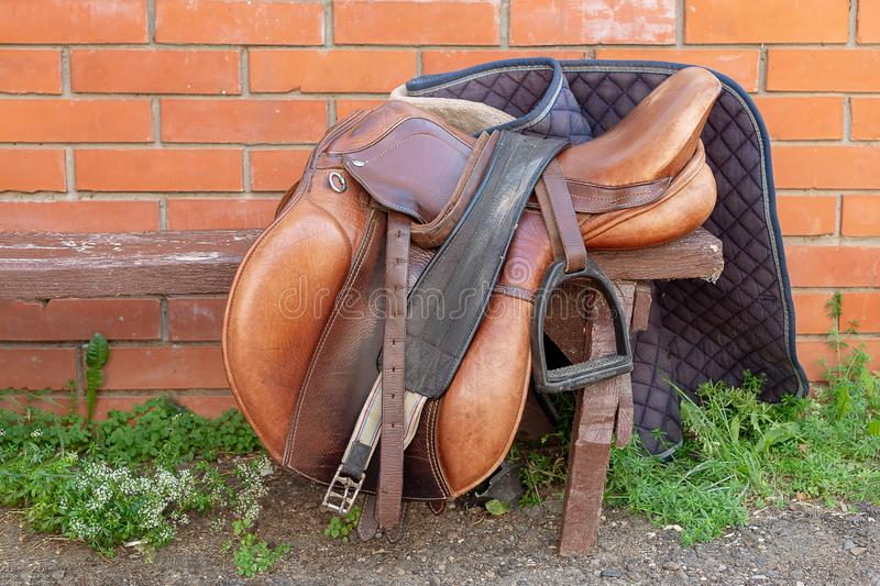 A brown saddle lies on a bench on a bright sunny day royalty free stock photo