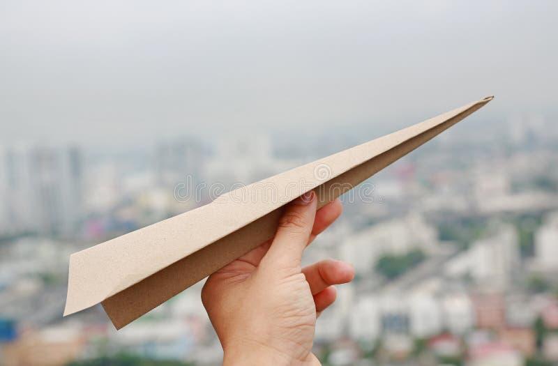 Brown samolotu rakiety papier w ręka fałdzie sukces na plamy tle miastowy, pojęciu dla biznesu i podróży roślinie, zdjęcie stock