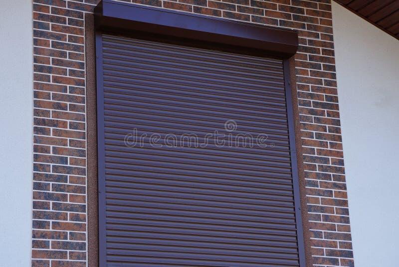 Brown schloss rollt auf dem Fenster in der Wand einer Backsteinmauer lizenzfreie stockfotografie