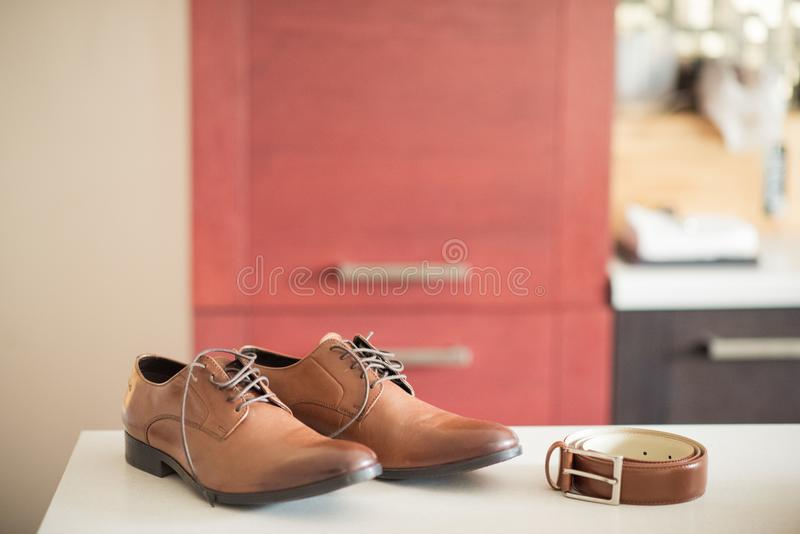 Brown-Schuhe und -gurt erwarten den vorwegnehmenden Bräutigam und heiraten Dekor stockbilder