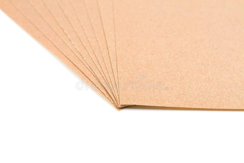 Brown sheet sandpaper. Brown sheet sandpaper for wood work stacked isolated on white background royalty free stock photo
