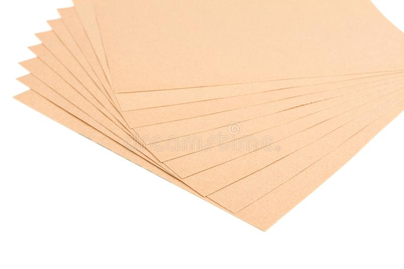 Brown sheet sandpaper. Brown sheet sandpaper for wood work stacked isolated on white background stock photography
