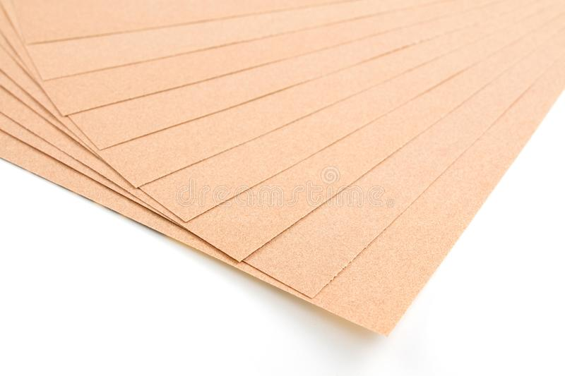 Brown sheet sandpaper. Brown sheet sandpaper for wood work stacked isolated on white background royalty free stock photos