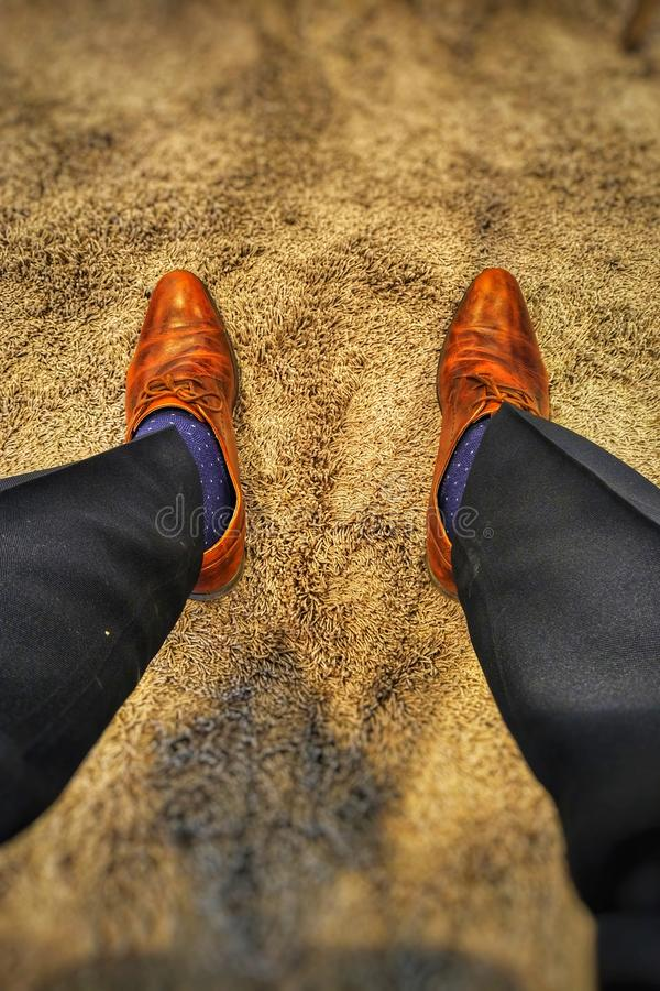 Brown Shoes Blue Socks Black Trousers. Brown Shoes Blue Starry Socks Black Trousers Pants on a Grey threaded carpet attire royalty free stock photography