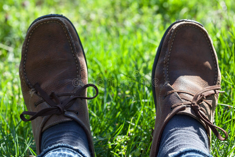 Brown shoes in the grass. Man in brown shoes lying in the green grass royalty free stock image
