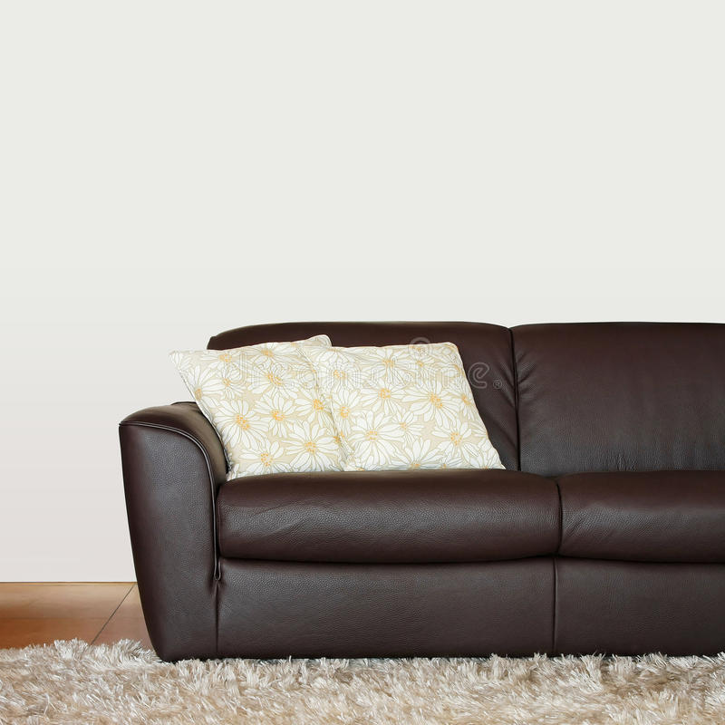 Brown sofa part. Part of brown leather sofa with pillows stock image