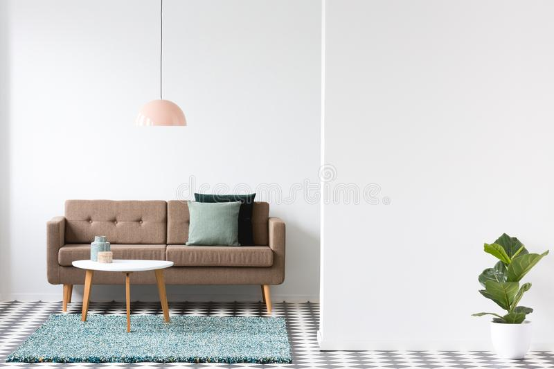 Brown sofa, pillows, coffee table and lamp in a living room interior next to an empty wall and plant. Place for your poster or royalty free stock image