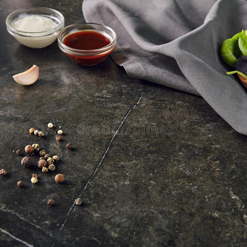Brown Soy Sauce and White Mayonnaise Sauce with Garlic and Fragrant Herbs on Dark Marble Background. Black Stone Flat Lay Frame with Spices for Recipe Template royalty free stock images