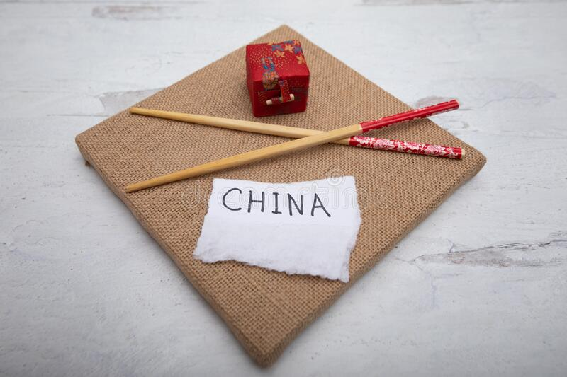 Brown square canvas with oriental chopsticks piece of white paper with the word China written on sign. Brown square burlap canvas with oriental chopsticks piece royalty free stock image