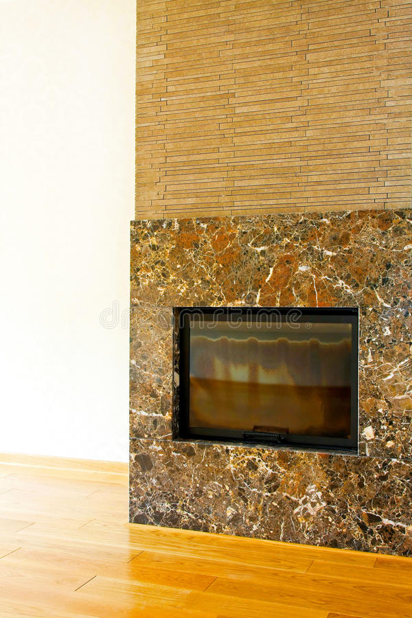 Brown stone fireplace. Brown stone and marble fireplace in living room royalty free stock photos