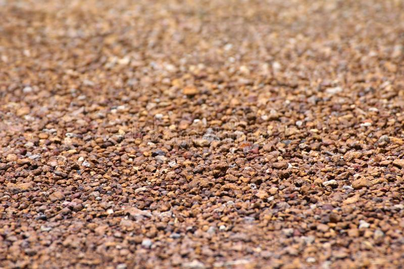 Brown stone grit scree, stone floor grit scree for background, floor surface rock materials scree texture, brown gravel stone royalty free stock photo