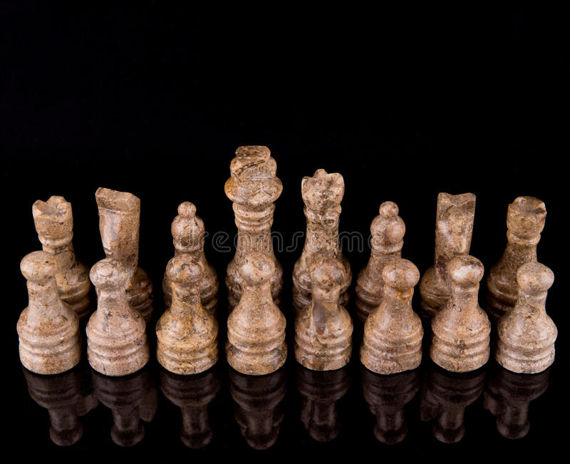 Brown Stone Made Chess Set II. Brown pieces of stone made chess set on black background royalty free stock photos