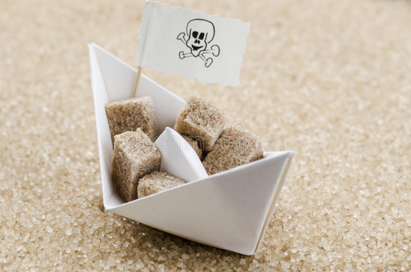 Brown sugar cubes on a boat in a brown sugar sea. Brown sugar cubes on a paper boat in a brown sugar sea stock photo