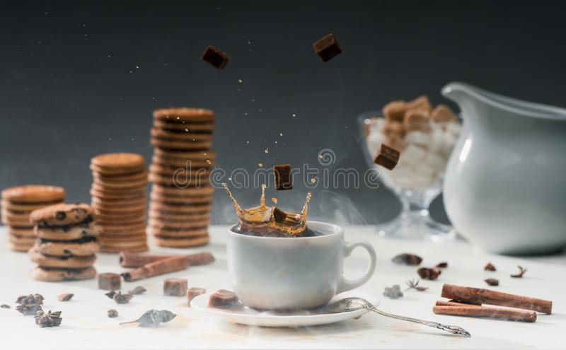 Brown sugar cubes falling in cup with black coffee on table with cookies. And spices royalty free stock images