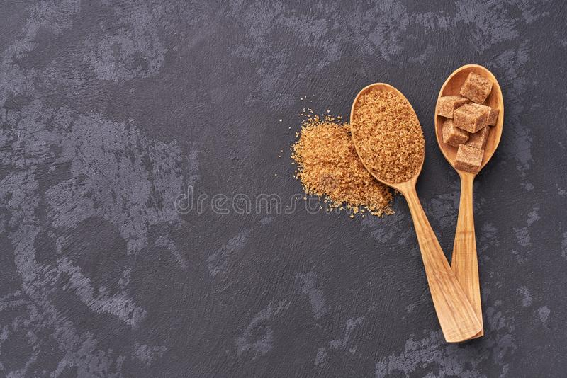 Brown sugar cubes and granulated sugar in two spoons with white sugar on black table.Flat lay royalty free stock images