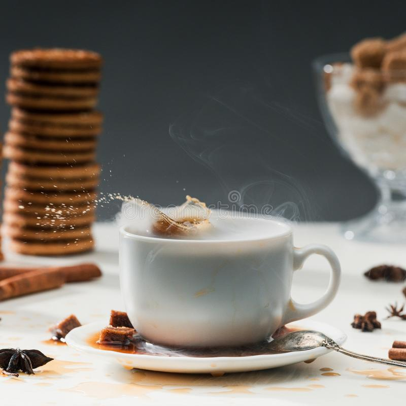 Brown sugar cubes splashing into coffee cup on table with cookies. And spices royalty free stock photos