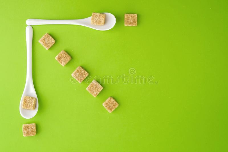 Brown sugar cubes and white spoons on greenery background arringed in rows. Top view. Flat lay. Copy space for text. royalty free stock photos