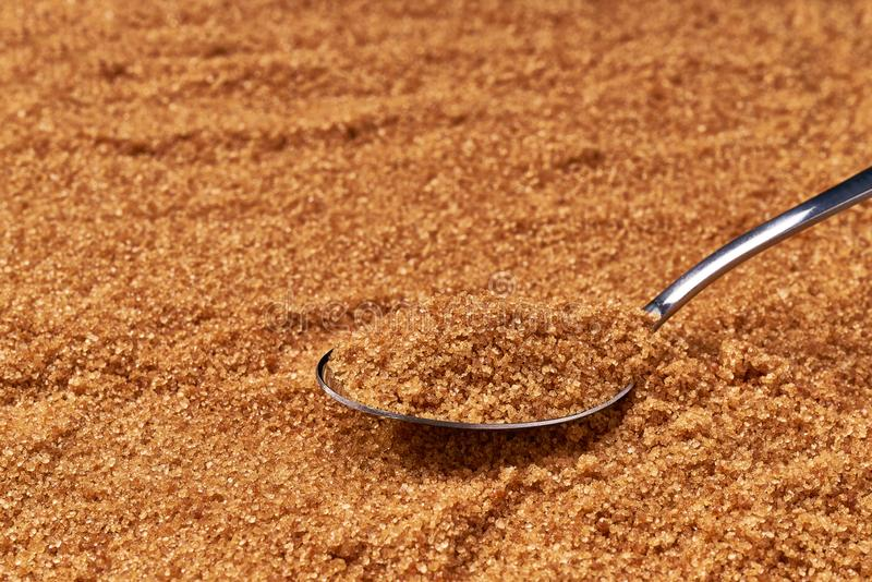 Brown sugar in metall spoon on the sugar background. Close-up royalty free stock photography