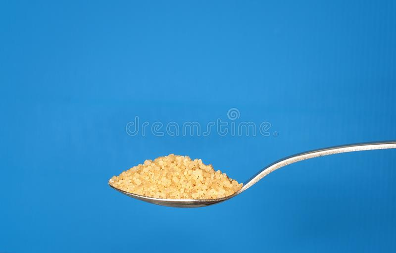 Brown sugar on metallic teaspoon. On blue background royalty free stock photography
