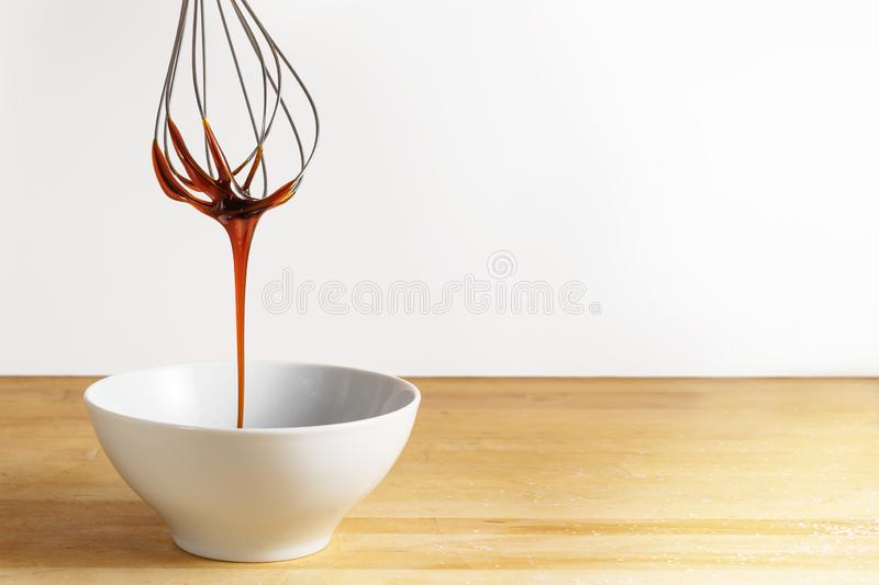 Brown sugar syrup flows from a wire whisk into a white bowl, wooden table and bright background with large copy space royalty free stock photos