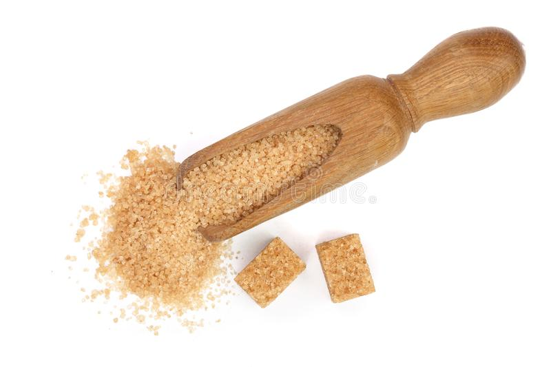 Brown sugar in wooden scoop isolated on white background. Top view. Flat lay stock photography