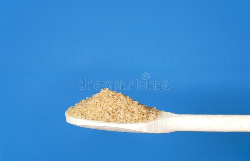Brown sugar on wooden teaspoon. On blue background royalty free stock photos