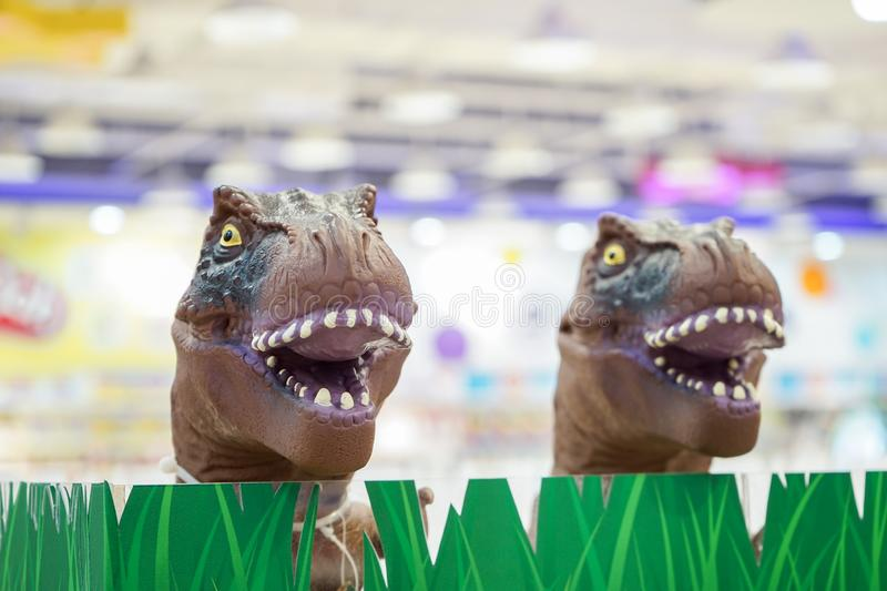 2 brown t-rex model toys head up from plastic grass in the kids shop, Bangkok department store, Thailand stock photos