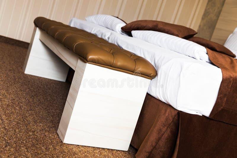 Brown tapizó el escabel de cuero en una cama imágenes de archivo libres de regalías