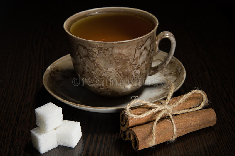 Brown tea cup and saucer, a bundle of cinnamon, sugar stock image