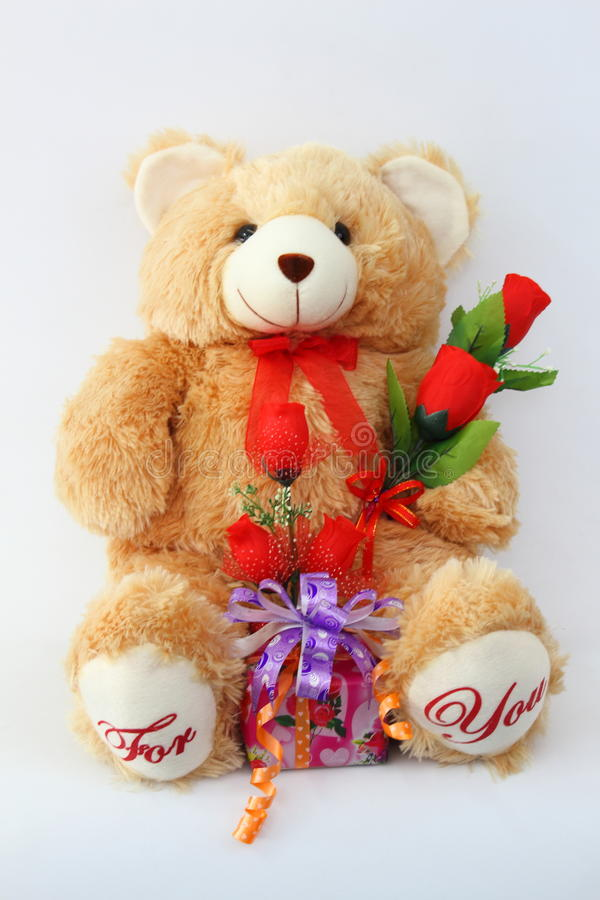 Brown teddy bear with a red rose and a gift box. stock photo