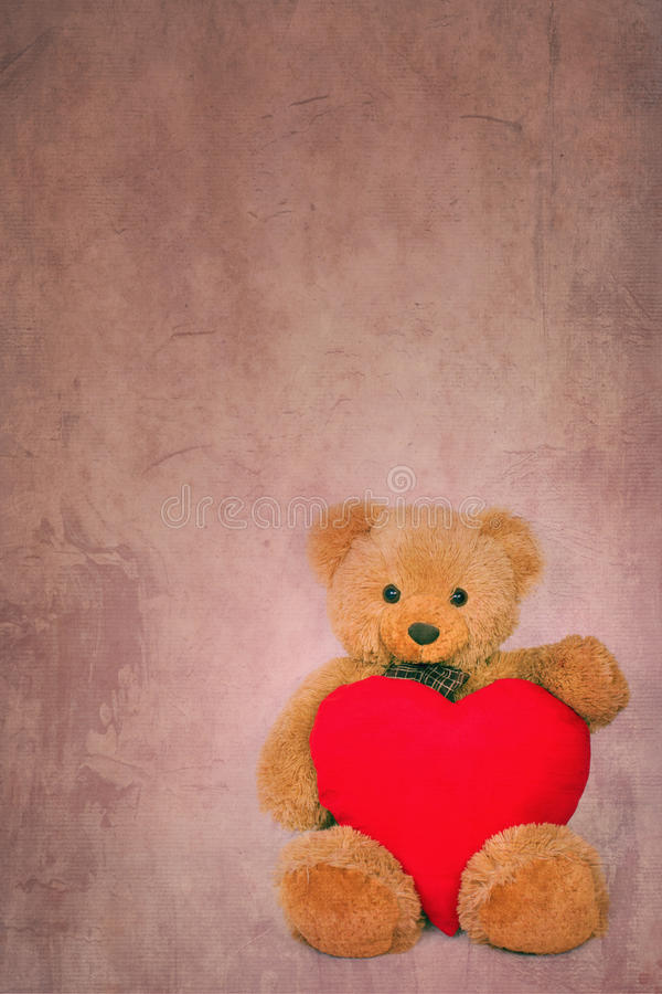 Brown teddy bear with soft heart on textured background royalty free stock photo