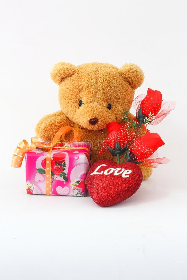 Brown teddy bear on a white background. Brown teddy bear with a red rose and a gift box on a white background royalty free stock images