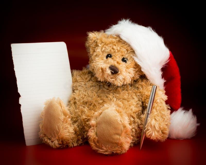 Brown Teddy Bear Writing uma letra a Santa Claus fotos de stock