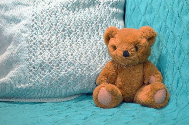 Brown-Teddybär, der auf einem blauen gestrickten Hintergrund sitzt lizenzfreie stockfotos
