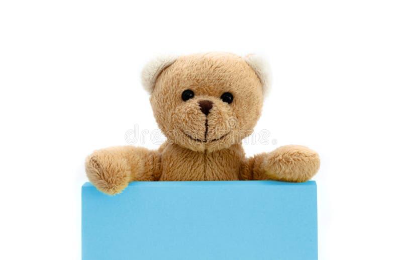 Brown-Teddybär, der mit den zwei Händen eine Anmerkung in der blauen Pastellfarbe mit leerem Raum für Textnachricht hält stockfoto