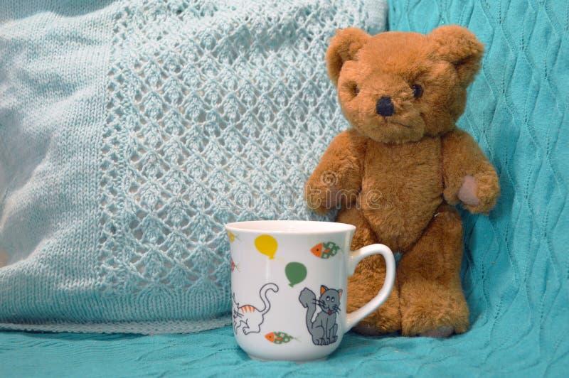 Brown-Teddybär, der nahe bei einer Schale steht stockfotografie