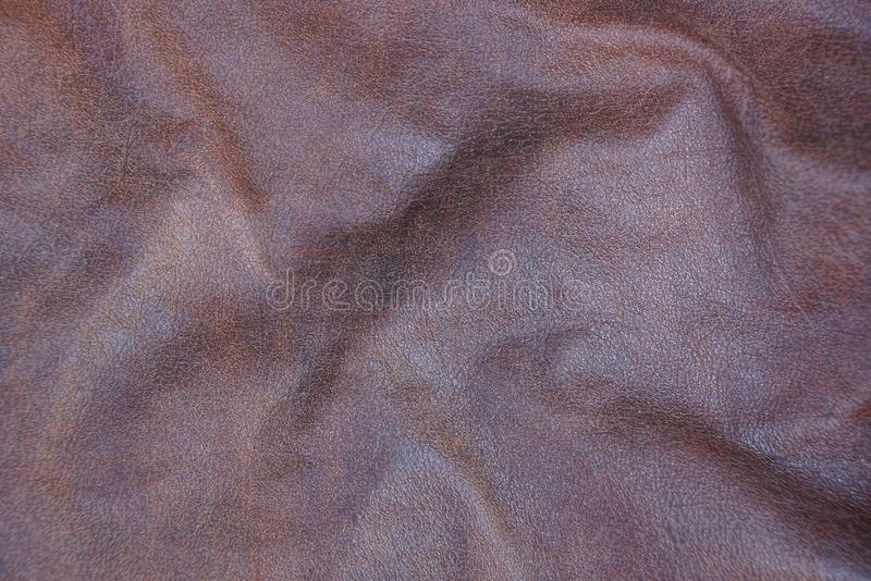Brown texture of crumpled leather on clothes. Brown background of crumpled leather on clothes royalty free stock photos