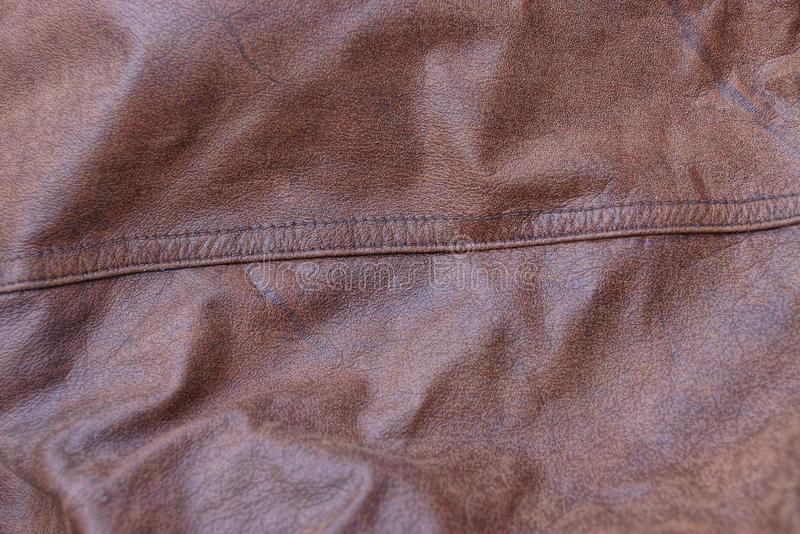 Brown texture of crumpled leather with a seam on clothes. Brown background of crumpled leather with a seam on clothes stock image