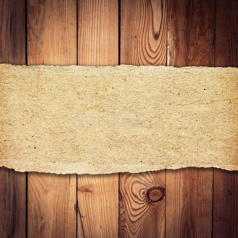 Brown torn paper on wood background and texture stock image