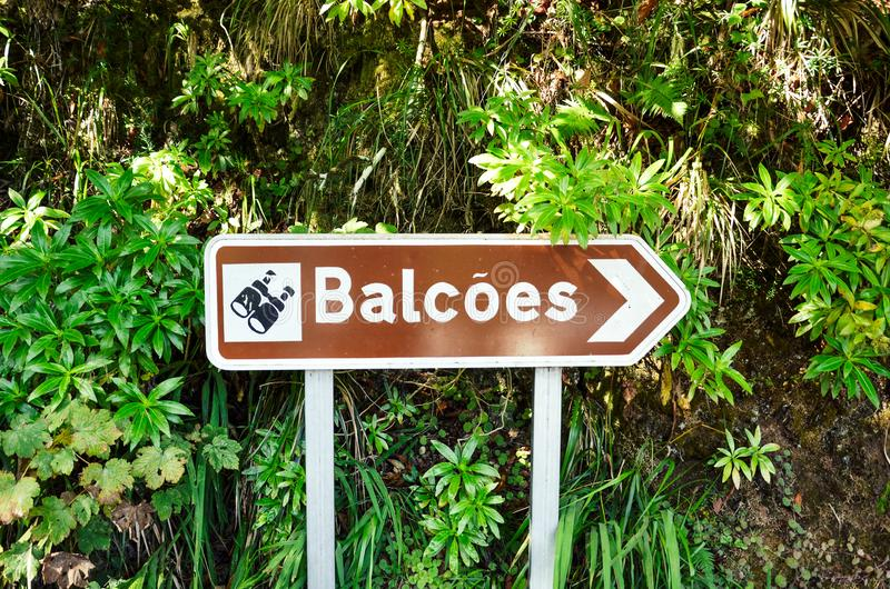 Brown tourist sign giving direction to the famous Levada dos Balcoes Trail in Madeira, Portugal. Information sign, marking system. Green forest in the royalty free stock images