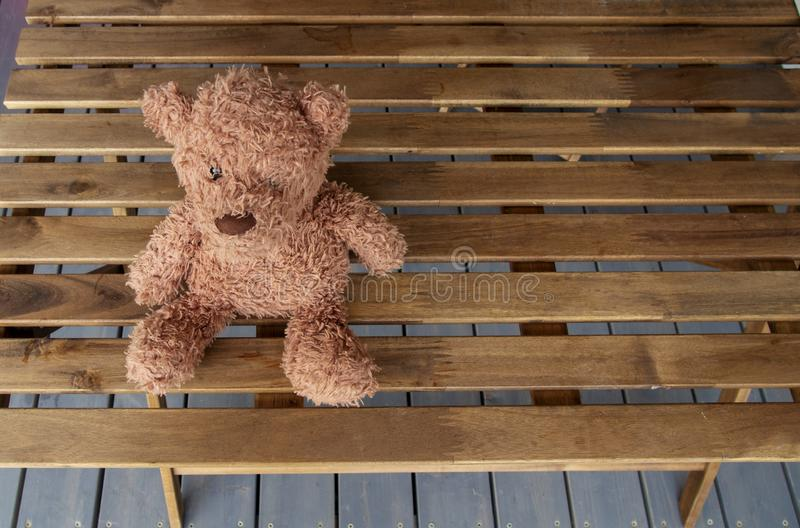 A brown toy bear sits on a wooden table on the terrace of a country house. Horizontal orientation, space for text.  royalty free stock photo