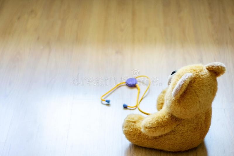 Brown toy soft bear with phonendoscope on brown background childhood concept.  stock photography