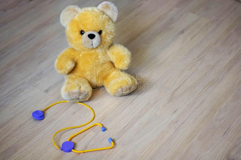 Brown toy soft bear with phonendoscope on brown background childhood concept.  royalty free stock photo