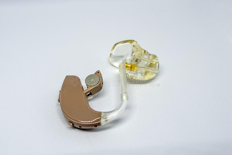Brown and translucent hearing aid against a white background. royalty free stock image