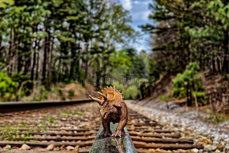 Brown triceratops dinosaur walking on railroad tracks. Brown triceratops walking on railroad tracks stock photography