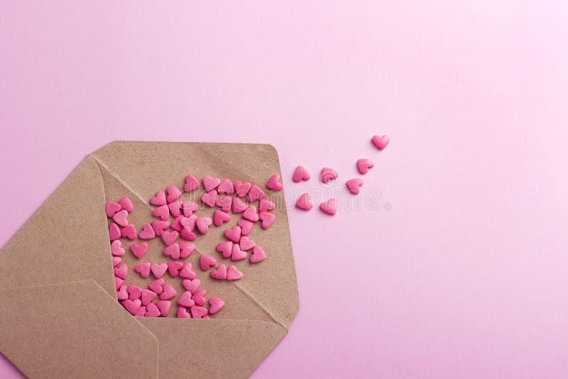 Brown-Umschlag mit purpurroten Herzen auf rosa Papier- oder Papphintergrund lizenzfreie stockbilder