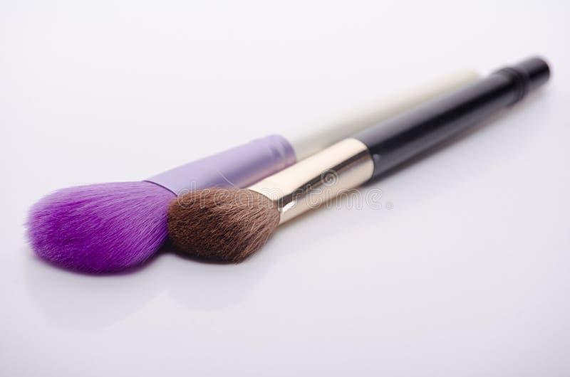Brown und purpurrote Make-upbürsten auf weißem Hintergrund, Abschluss oben lizenzfreies stockbild