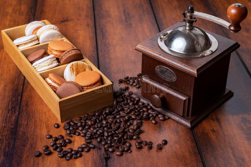 Brown und weiße französische Makronen in einem Bambuskasten mit verschütteter Kaffeebohne- und WeinleseKaffeemühle über hölzernem stockbild