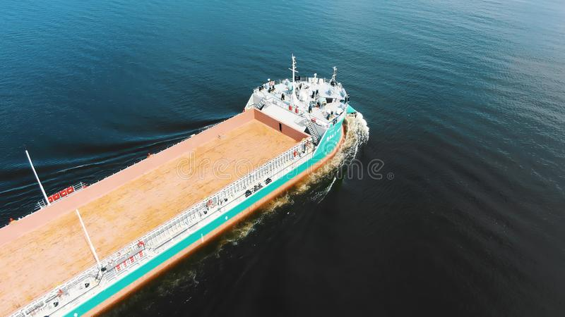 Brown unloaded freight vessel sails on deep blue sea water royalty free stock photo
